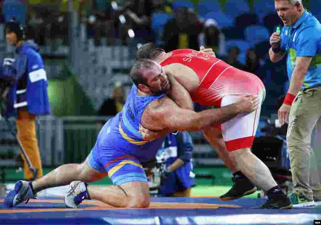 Levan Berianidze of Armenia (in blue) in action against Ibrahim Saidau of Belarus during the men's freestyle wrestling 125-kilogram-bronze medal bout. Turkey's Taha Akgul won gold, with Ghasemi taking silver, and Saidau and Geno Petriashvili of Georgia sharing the bronze.
