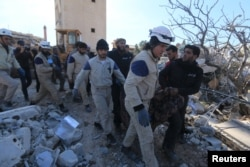 Rescue workers carry a dead body from a destroyed hospital supported by Medecins Sans Frontieres hit by missiles in Syria's Idlib Province on February 16.