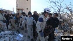 """Құтқарушылар тобы әуе шабуылына ұшыраған """"Шекарасыз дәрігерлер"""" ұйымы ауруханасында мерт болған адамның сүйегін әкеле жатыр. Идлиб, Сирия, 16 ақпан 2016 жыл."""
