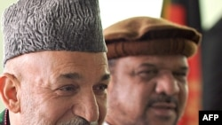 President Hamid Karzai (left) with Mohammad Qasim Fahim at the Independent Election Commission in Kabul in May