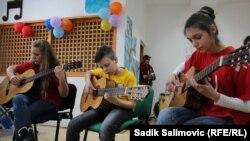 Гитара үйреніп отырған оқушылар. (Көрнекі сурет)