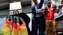Protesting homophobia in Russia on two continents: an LGBT rights protester in Moscow (left) and one in New York.