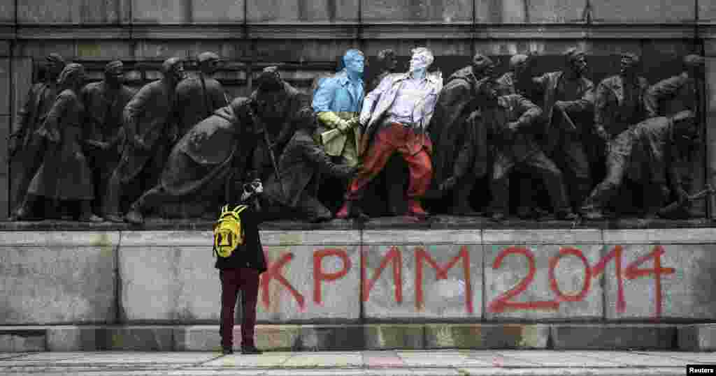 A man takes pictures of figures of a Bulgarian communist-era monument painted in the colors of the Ukranian and Polish flags by unknown people in Sofia. (Reuters/Stoyan Nenov)