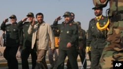 Iranian President Mahmoud Ahmadinejad, third left, reviews Basij paramilitary volunteers, affiliated to the elite Revolutionary Guard, during their parade ceremony, as he is accompanied by Revolutionary Guard's commander Yahya Rahim Safavi, second left, T