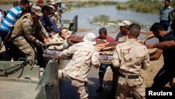 A wounded displaced man is evacuated by Iraqi forces across the Tigris.