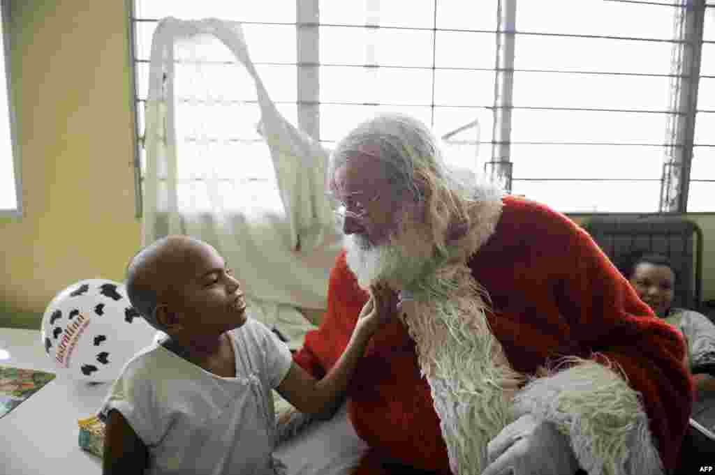 Icelandic philantropist Einar Sveinsson, dressed as Santa Claus, speaks with a patient at the oncology ward during a visit to the Benjamin Bloom National Children Hospital in San Salvador, El Salvador. Sveinsson has visited the hospital prior to Christmas every year since 2001 to give gifts to the patients. (AFP/Jose Cabezas)