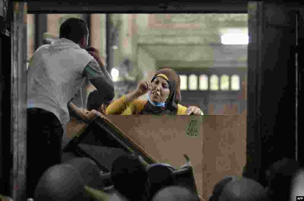 An Egyptian woman talks to policemen from the inside of Cairo's Al-Fateh Mosque where Islamist supporters of ousted President Muhammad Morsi were holed hole up on August 17. Egyptian secuity forces cleared the building that evening. (AFP/Mohamed El-Shahed)