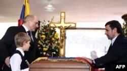 Найліпші друзі небіжчика Уго Чавеса біля його труни: президент Білорусі Олександр Лукашенко і його позашлюбний син Микола (л), президент Ірану Махмуд Ахмадінеджад (п), 8 березня 2013 року