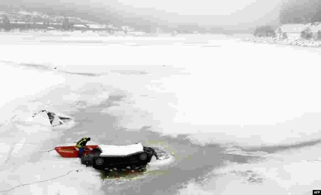 A firefighter works on the rescue of a car stuck in the frozen Schluchsee Lake in the Black Forest region of southern Germany. According to the police, the car was empty. (AFP/Patrick Seeger)