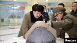 Лидер Северной Кореи Ким Чен Ын рассматривает ядерную боеголовку после повторного испытания. Март 2016 года.