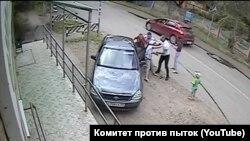 """Полицейские силой пытаются посадить в машину Игоря Скоротягу и его мать. Скриншот из видео, опубликованного в ютуб-канале """"Комитета против пыток"""""""