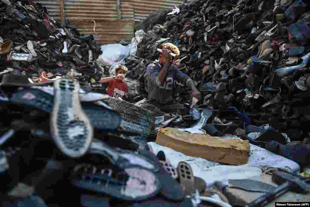 Laborers dismantle old shoes for recycling at a workshop in Karachi, Pakistan. (AFP/Rizwan Tabassum)