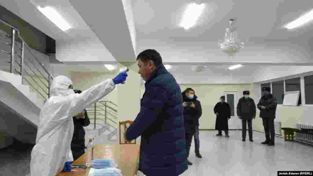 В некоторых избирательных участках члены комиссии одеты в спецодежду, проверяют температуру тела граждан