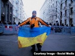 Сергій Нужненко тримає в руках заплямований кров'ю прапор, в який був загорнутий 1 грудня