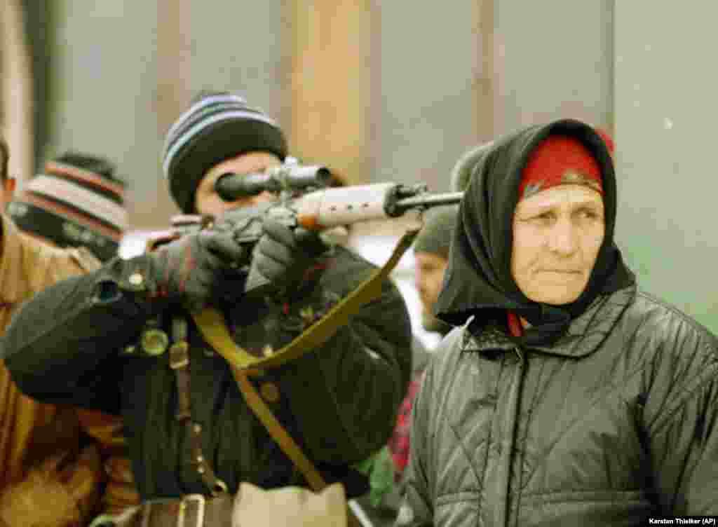 Чеченский снайпер наводит прицел. Женщинам рядом с ним наблюдает за снайпером федеральных войск, обстреливающим уличный рынок на окраине Грозного. 25 января 1995 года.