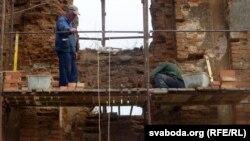 Будаўнікі выбіваюць спарахнелыя цаглінкі і мяняюць на новыя