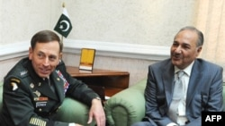 Pakistani Defense Minister Ahmed Mukhtar (right) meets with U.S. General David Petraeus in Rawalpindi.