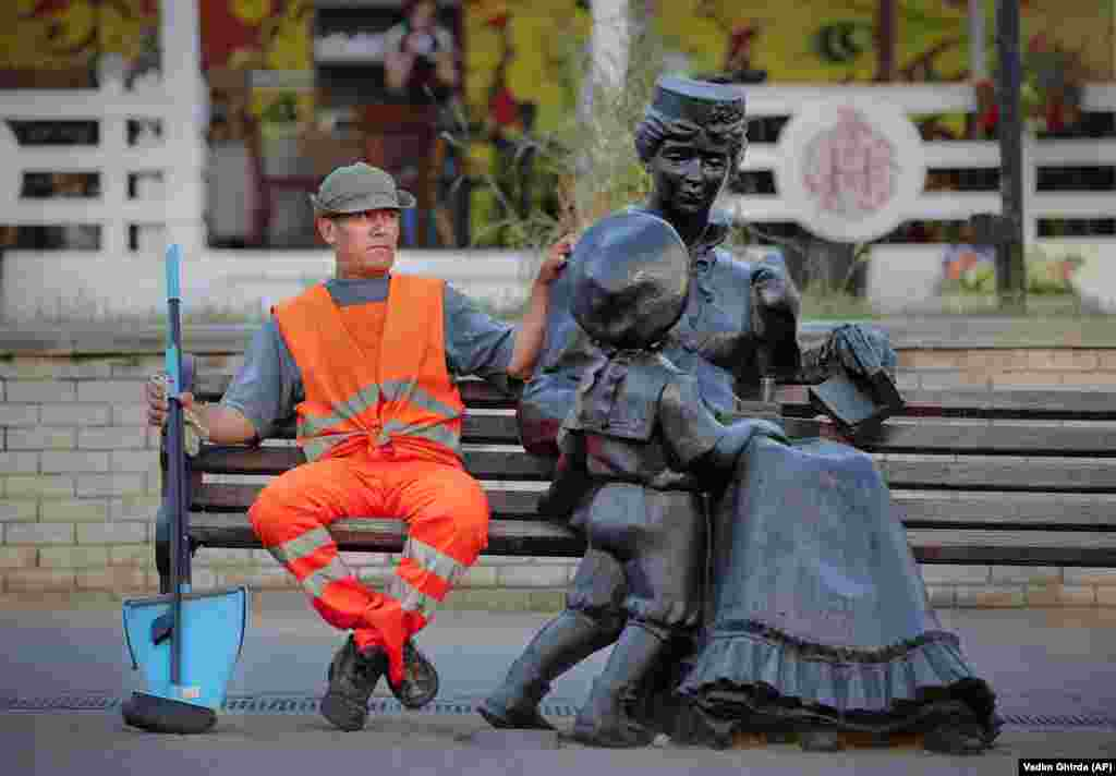 A municipal worker sits on a bench next to a statue in Nizhny Novgorod, Russia, during the 2018 soccer World Cup. (AP/Vadim Ghirda)