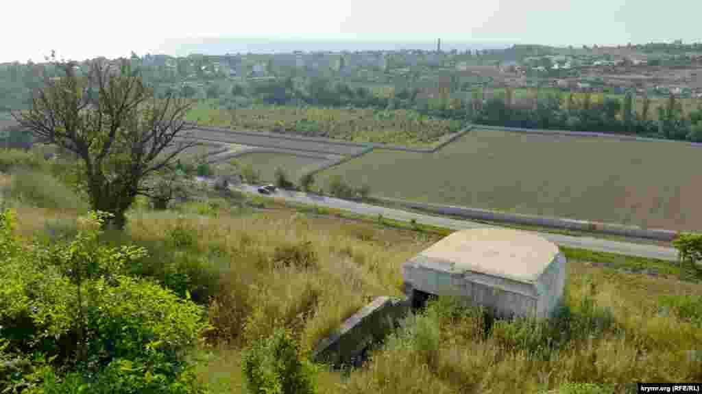 З пагорба територія проглядається на десятки кілометрів, на передньому плані– кулеметний дзвт (довгострокова замаскована вогнева точка)