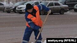 Рабочий коммунального предприятия на уборке улицы от снега в Астане.