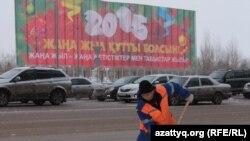 Астанада көшені қардан тазалап жүрген коммуналдық мекеме жұмысшысы (Көрнекі сурет).