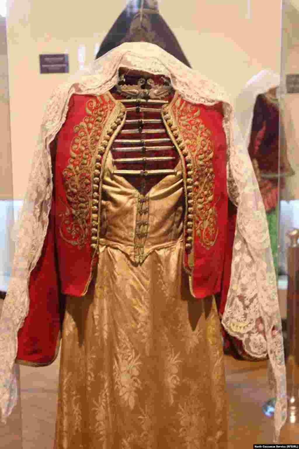 Это грузинское платье XIX века украшено нагрудниками (или чапрастами), которые привозились из Черкесии и Дагестана.