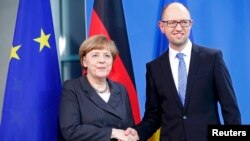 German Chancellor Angela Merkel (left) shakes hand with Ukrainian Prime Minister Arseniy Yatsenyuk after talks at the Chancellery in Berlin on April 1.