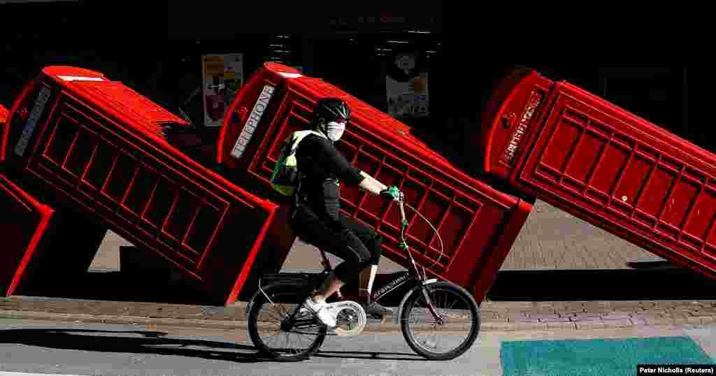 Велосипедист їде в захисній масці повз інсталяцію «Out of Order» скульптора Девіда Мача. Дванадцять червоних телефонних будок класичної моделі, які є настільки ж упізнаваним символом Великої Британії, як і поштові скриньки та двоповерхові автобуси, покладені на бік за «принципом доміно»