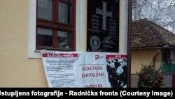 """Spomen-ploča HOS-a s natpisom """"Za dom spremni"""" u Jasenovcu, ispod protestni plakat Radničke fronte"""