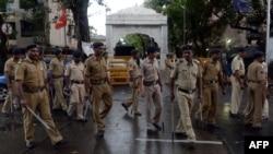 Индийские полицейские стоят посреди дороги в городе Мумбаи. 30 июля 2015 года. Иллюстративное фото.