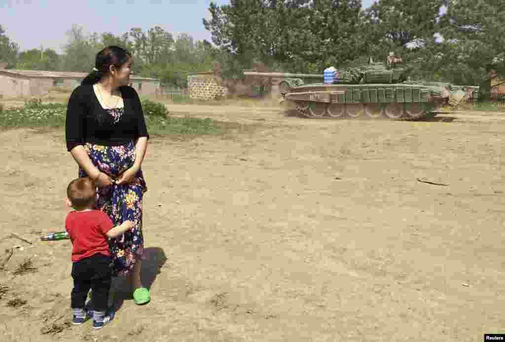Женщина с ребенком наблюдает за передвижением военной техники через поселок. Конвой едет в Кузьминский - тренировочную военную базу на границе России и Украины - 26 мая 2015