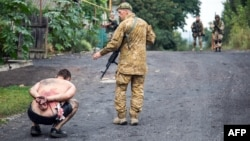 Ukrainian forces detain a pro-Russia separatist in the village of Chornukhine in the Lugansk region in August 2014.