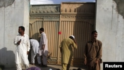 Local residents on May 4 try to look past the gates into the compound where Al-Qaeda leader Osama bin Laden was killed in Abbottabad, Pakistan.