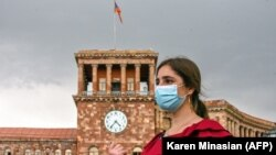 A woman wearing a protective face mask walks in central Yerevan.