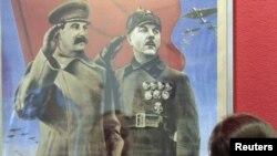 Посетитель выставки «Победа» смотрит на плакат с изображением Иосифа Сталина. Москва, 23 апреля 2010 года.