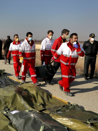 IRAN -- Rescue workers carry the body of a victim of a Ukrainian plane crash in Shahedshahr, southwest of the capital Tehran, Iran, Wednesday, Jan. 8, 2020.