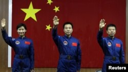 Қытай астронавтары Лю Янг (сол жақта), Жинь Хайпенг (ортада) Лю Уанг (оң жақта). 15 маусым 2012 жыл.