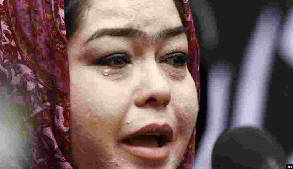 An Afghan woman cries as she condemns the killings.