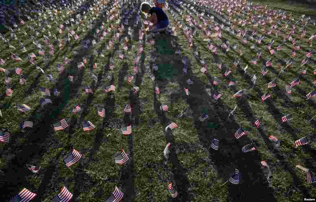 A girl plants some of the 3,000 flags placed in memory of the lives lost in the September 11, 2001 attacks at a park in Winnetka, Illinois. (Reuters/Jim Young)