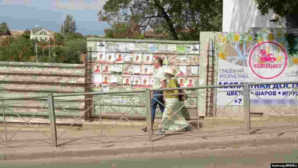 Чоловік у Севастополі задивився на політичну рекламу на паркані, 18 вересня