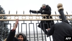 Торговцы бишкекского рынка, потерявшие работу, пытаются перелезть через ограду Дома правительства