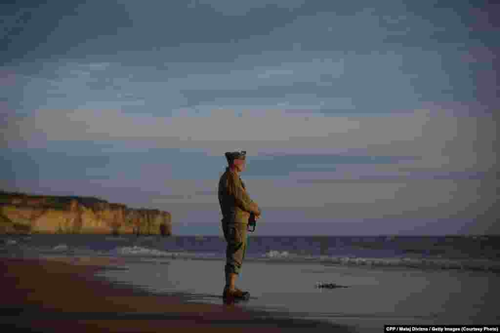 Honorable Mention, General News:Aman dressed in aWorld War II-eraU.S. uniform pays his respects tothose who died in the D-Day landings in Normandy, France, onJune 6, 2014, the 70th anniversary of the Allied invasion. (Denik/Martin Divisek)