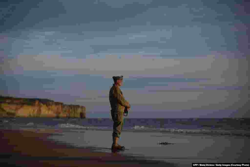 """Një burrë i veshur me uniformë të Luftës së Dytë Botërore, duke bërënderimet e tij për ata që vdiqën në Ditën -D, në tokat eNormandisë, Francë. Gjashtëqershori 2014, shënoi 70-vjetorin e pushtimit masiv të aleatëve. Kategoria""""Lajme të Përgjithshme"""", nga Martin Divisek, Denik."""