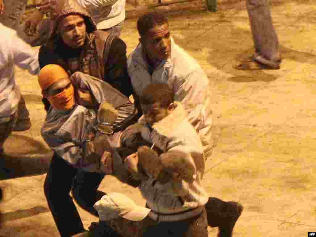 Demonstrators carry an injured protester during clashes with anti-riot police in Suez January 27.