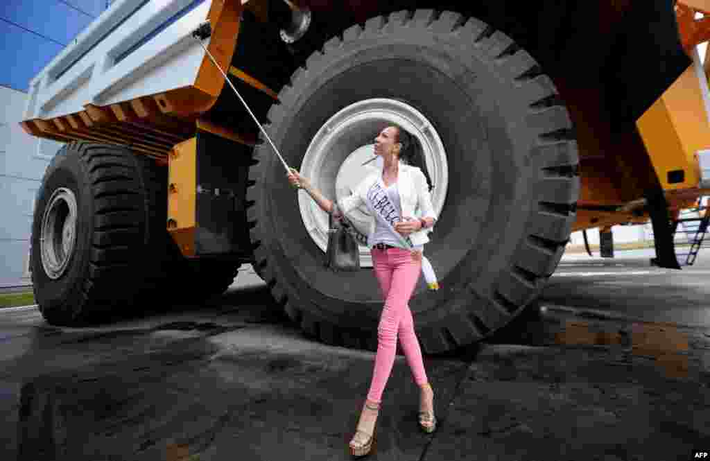 A participant in the Mrs. Universe 2015 contest takes a selfie as she stands close to a huge mining dump truck at the BelAZ plant in Zhodino, outside Minsk in Belarus. (AFP/Sergei Gapon)
