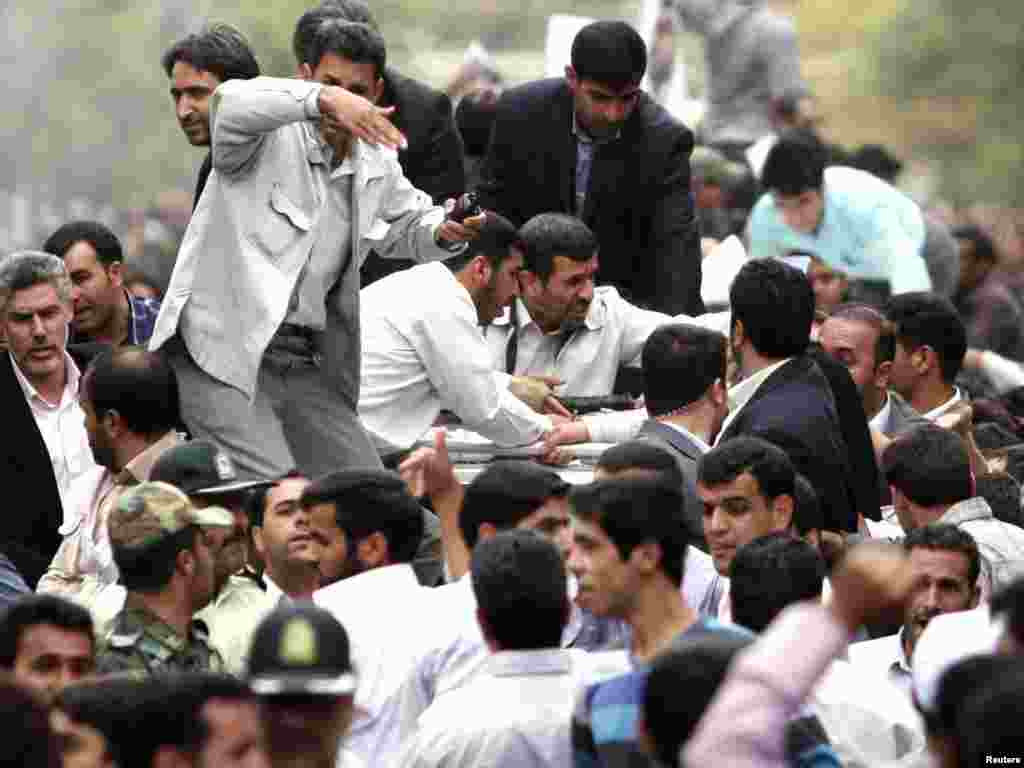 Bodyguards react after the sound of an explosion behind the entourage of Iranian President Mahmud Ahmadinejad (center) as he is welcomed in Hamadan, southwest of Tehran, on August 4. Reports say his motorcade was attacked by someone with a homemade explosive device. Iranian officials later denied the report. Photo by Reuters