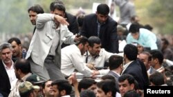 Bodyguards reacted to a burst of sound behind the entourage of President Mahmud Ahmadinejad (center) as he was welcomed to Hamedan on August 4.