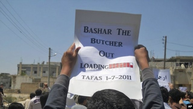 A protester holds up a placard during a demonstration against the Assad regime in village of Tafas on July 1.