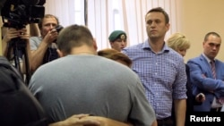 Pyotr Ofitserov (with back to camera) gives his wife a farewell embrace as Aleksei Navalny (facing camera) awaits custody after the verdict in the courtroom in Kirov on July 18.