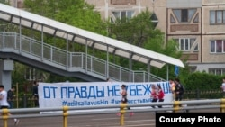 Люди, бегущие вдоль баннера с надписью: «От правды не убежишь». Алматы, 21 апреля 2019 года.